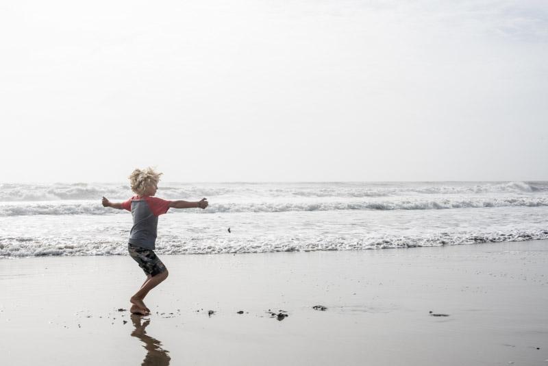boy-spinning-on-beach
