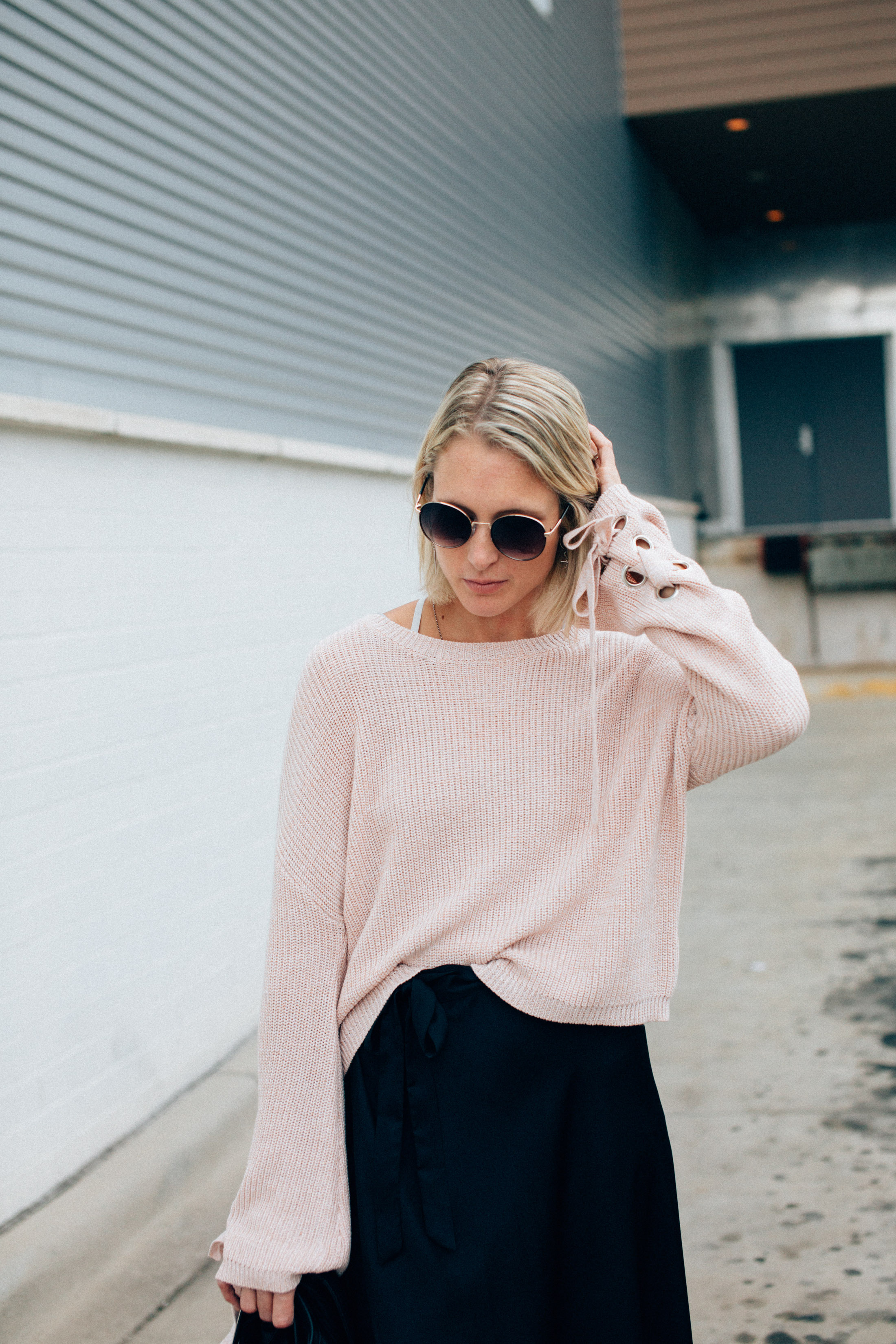 blush pink pullover sweater with black skirt