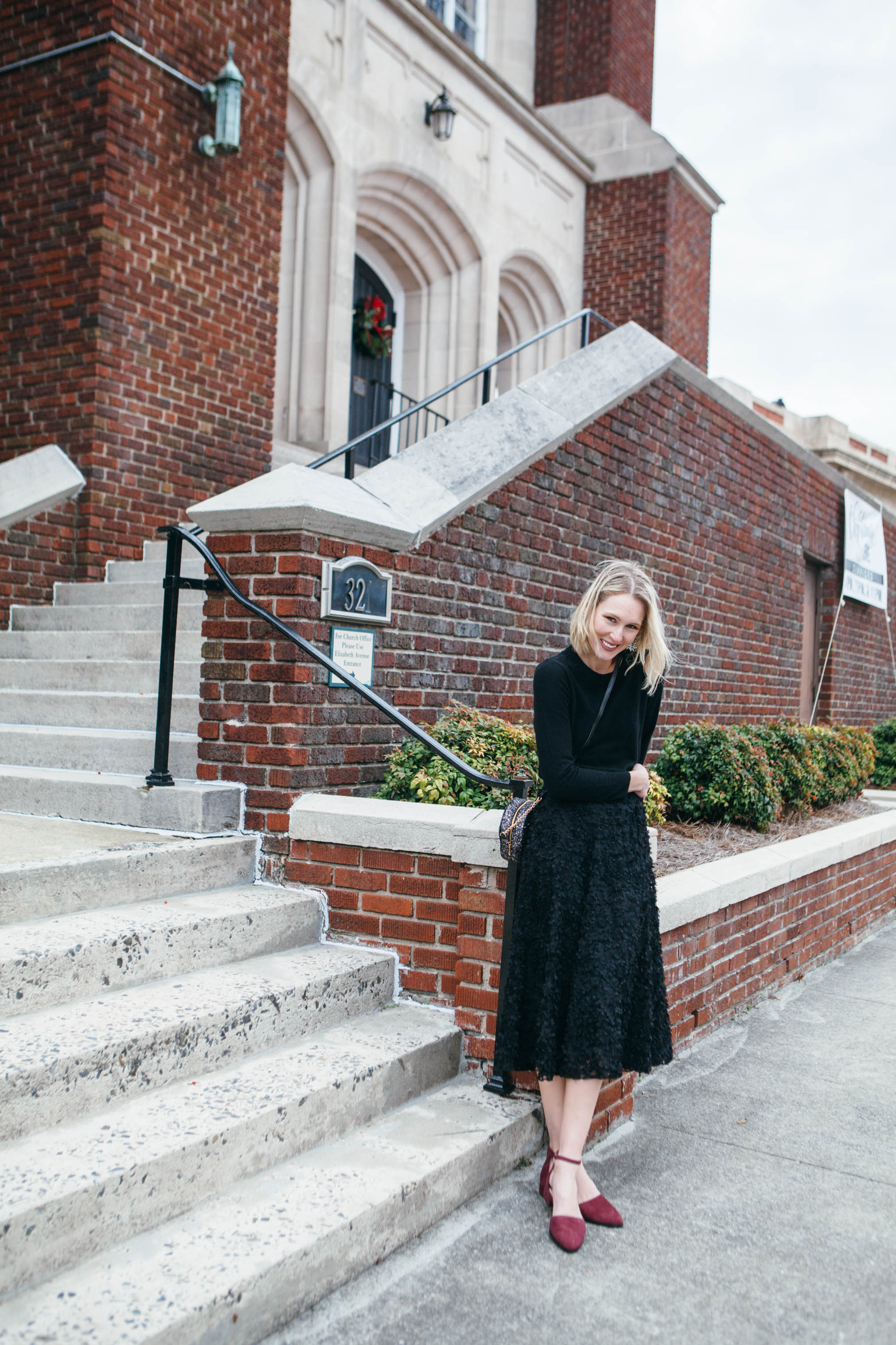 black sweater and midi skirt with burgundy flats