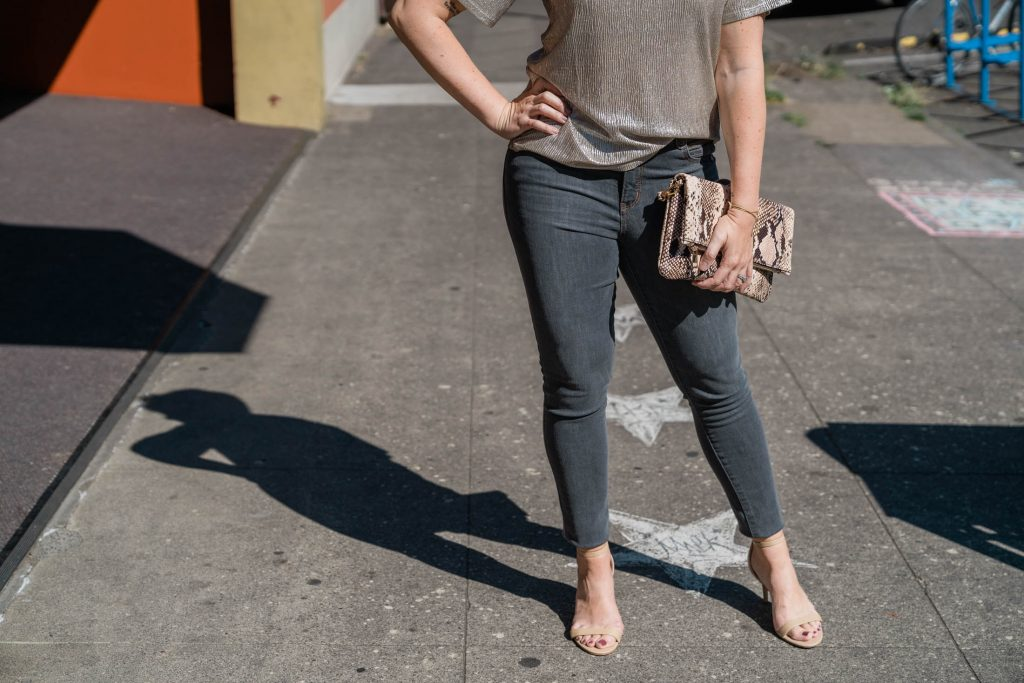 Mamas, when we find a top that totally makes our outfit — & it's unexpected — we call it a win. This metallic gold top + gray jeans combo is just that.